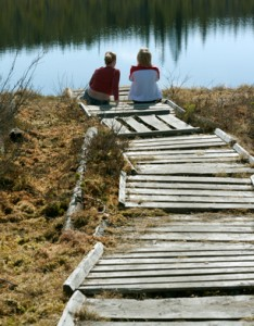 Western Canadian History. Two girls sit on pier talking about history, life, wellness